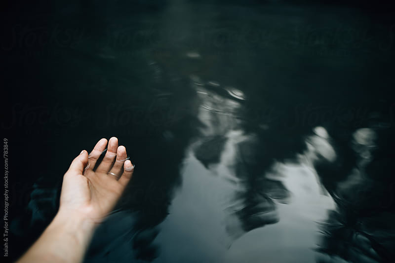 Open hand in body of water by Isaiah & Taylor Photography for Stocksy United
