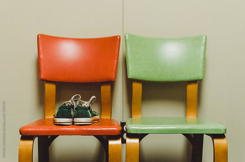 two retro chairs with a pair of green plaid sneakers by Deirdre Malfatto for Stocksy United