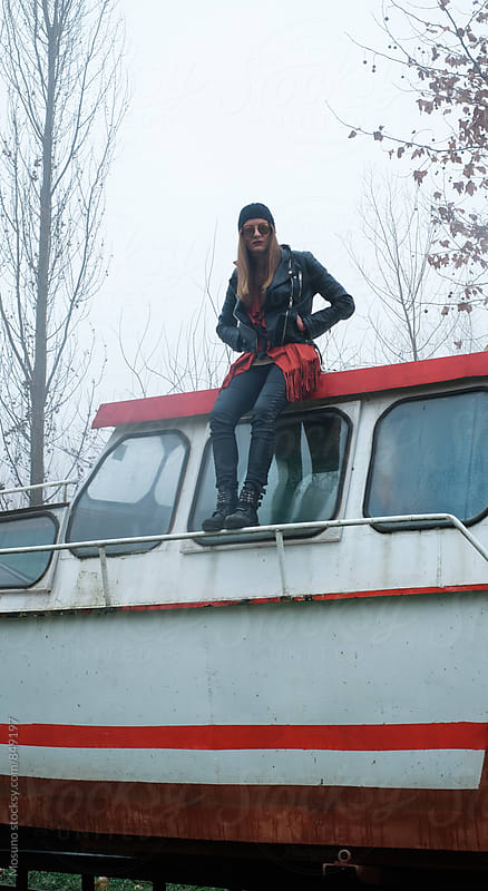 Urban Girl Standing on the Old Boat by Mosuno for Stocksy United
