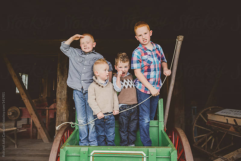 Four boys  (brothers) pretending to pirates in the back of a wagon by Rob and Julia Campbell for Stocksy United