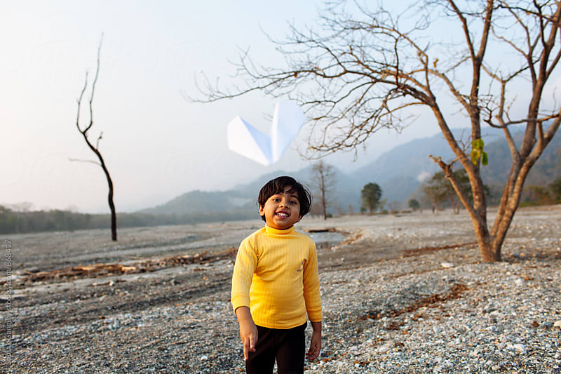 Child playing with paper plane by Saptak Ganguly for Stocksy United