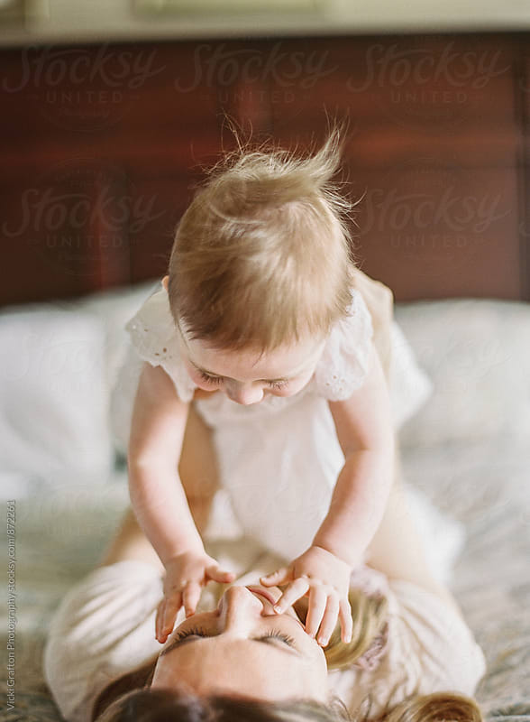 1 year old playing on bed with mom by Vicki Grafton Photography for Stocksy United