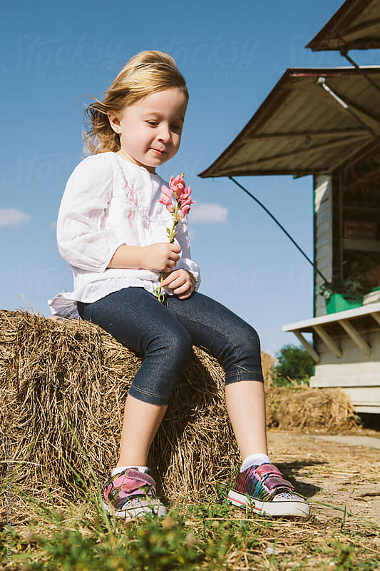 Little girl holding flowers by Stephen Morris for Stocksy United