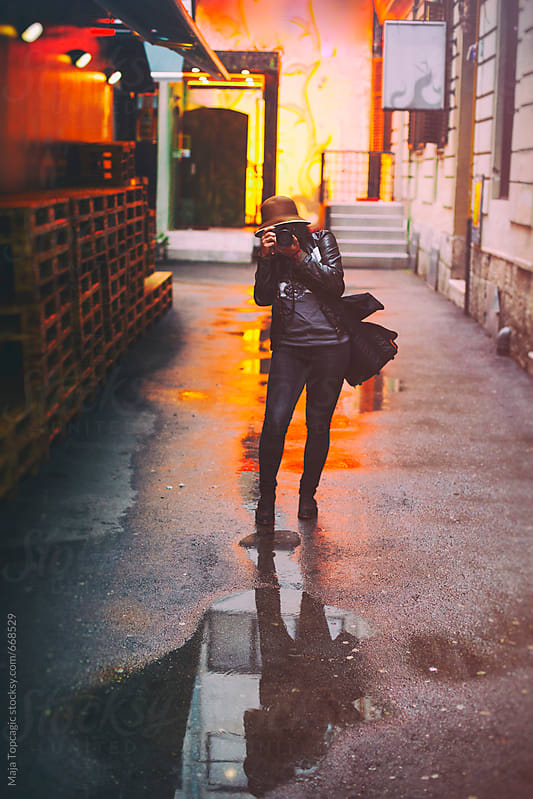 Young female photographer taking photos in the rain by Maja Topcagic for Stocksy United