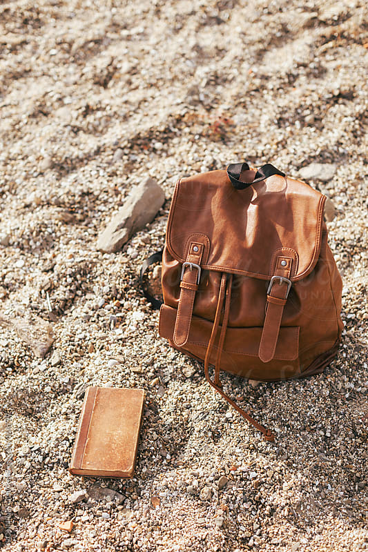 Leather backpack and old book in the sand of the beach. by BONNINSTUDIO for Stocksy United