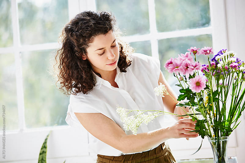 Woman Arranging Flowers In Vase At Home by ALTO IMAGES for Stocksy United