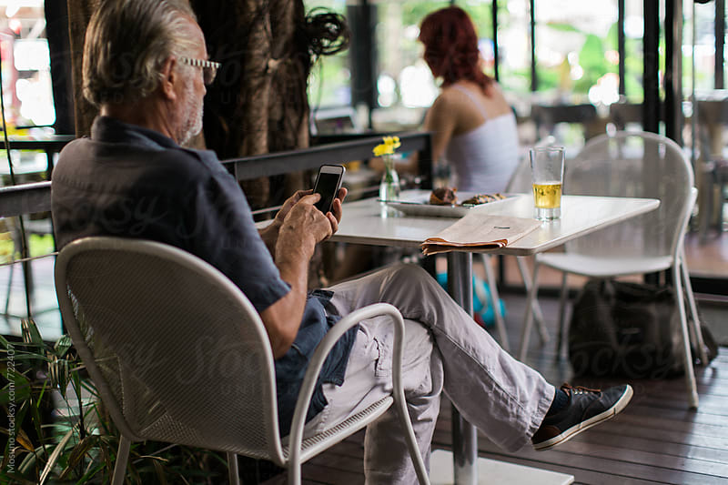 Senior Man Sitting in a Cafe and Checking His Phone by Mosuno for Stocksy United