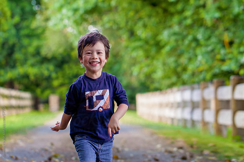 Little boy running excitedly towards the camera by Rowena Naylor for Stocksy United
