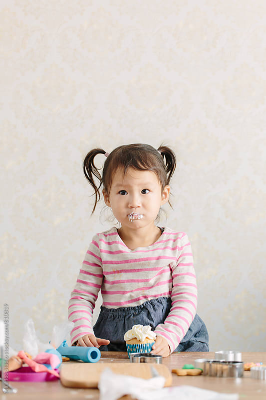 Toddler girl eating cupcake by MaaHoo Studio for Stocksy United