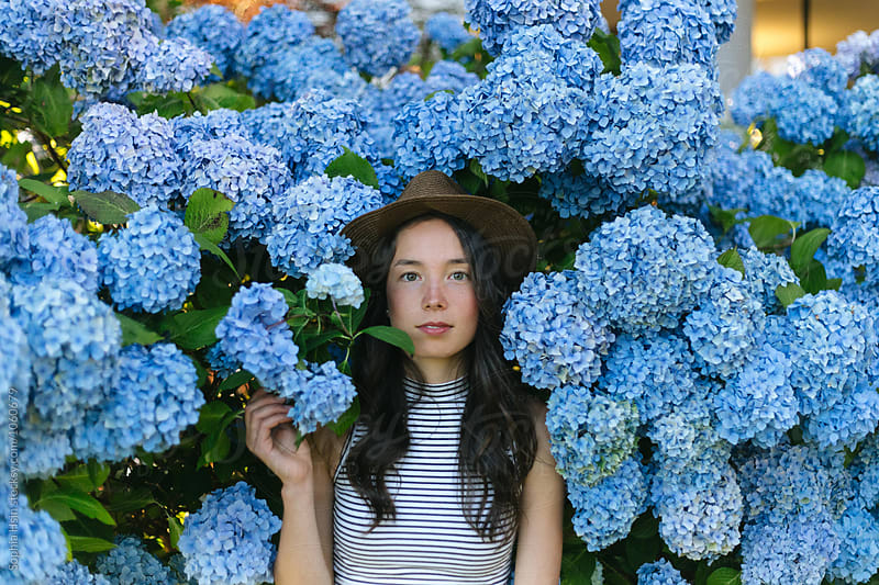 Girl in hat holding blue flowers by Sophia Hsin for Stocksy United