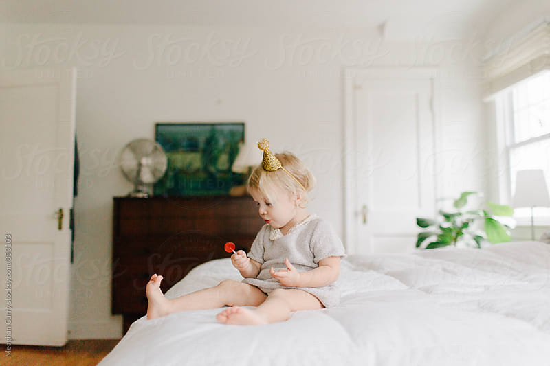little girl sits on a bed wearing a party hat and having a lollipop to celebrate her birthday by Meaghan Curry for Stocksy United