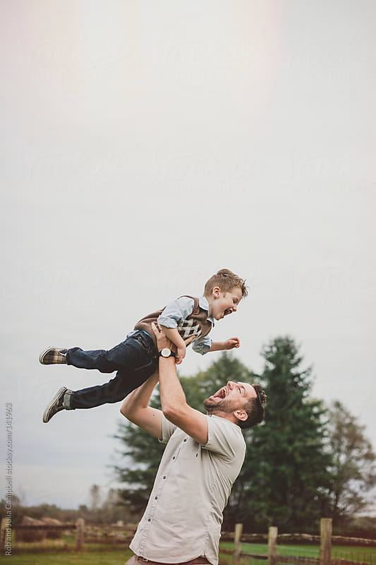 Dad throwing young son up in the air in farm field by Rob and Julia Campbell for Stocksy United
