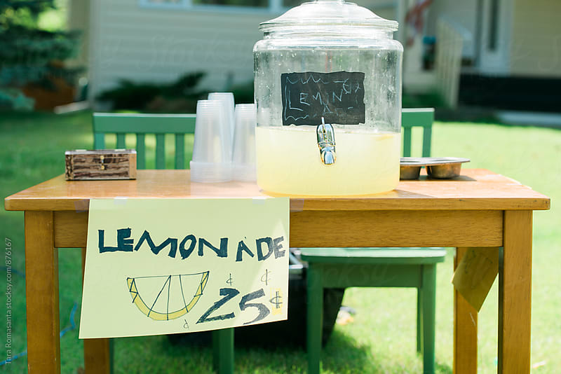 lemonade stand with hand lettered sign by child  by Tara Romasanta for Stocksy United