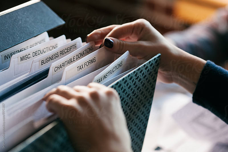 Taxes: Woman Digging Through Tax File Folder For Forms by Sean Locke for Stocksy United