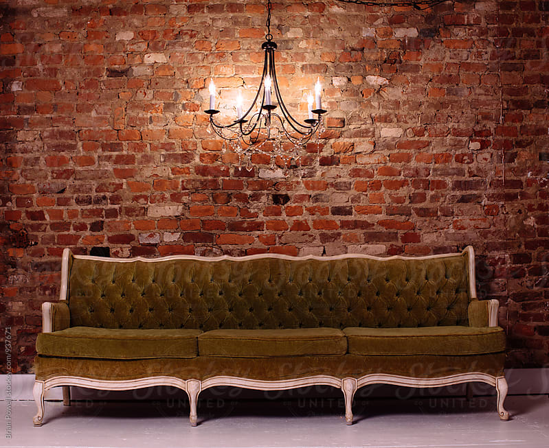 Chandelier with sofa and brick wall  by Brian Powell for Stocksy United