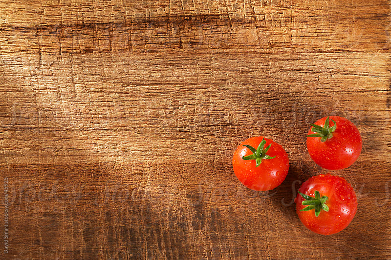 Whole tomatoes on rustic cutting board by David Smart for Stocksy United