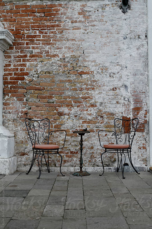 two chairs and a table against an old brick wall by Rene de Haan for Stocksy United