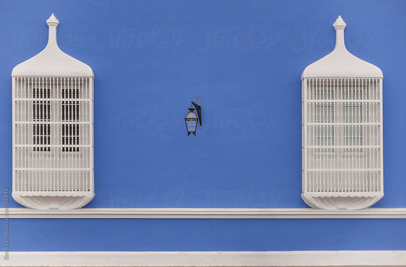 White Spanish colonial balconies on a rendered blue wall by Ben Ryan for Stocksy United