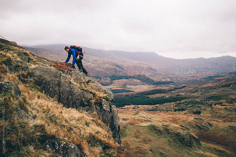 Mountaineer scrambles on edge of mountainside. by Liam Grant for Stocksy United