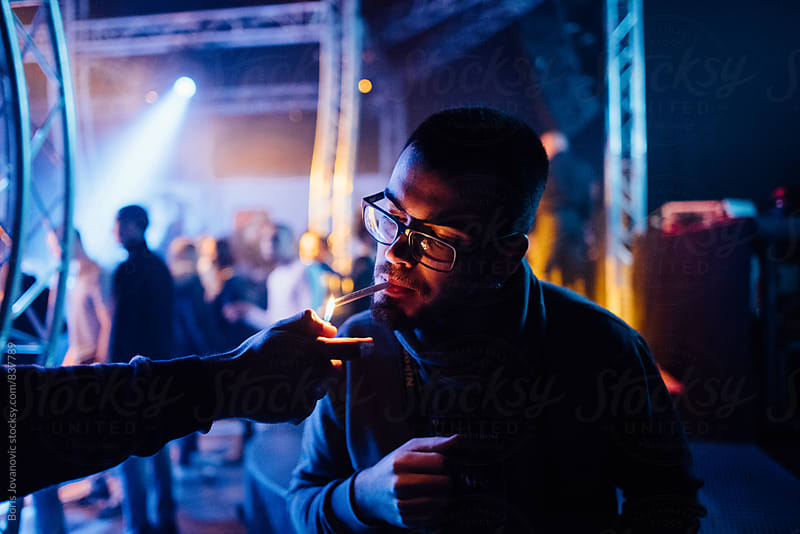 Man lighting up a ciggarette to another man by Boris Jovanovic for Stocksy United