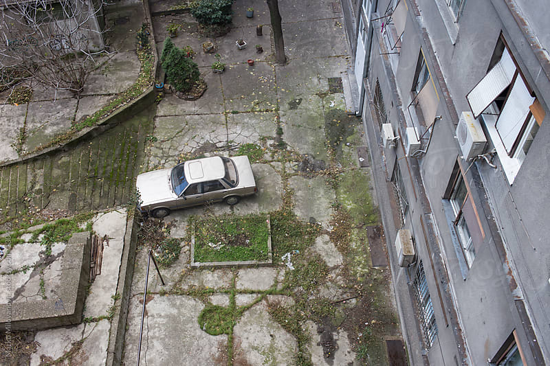 Parked car in old rustic garden by Marko Milovanović for Stocksy United