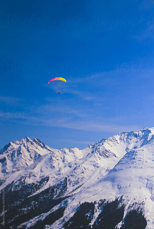 Paraglider flying in winter mountain landscape with snow by Soren Egeberg for Stocksy United
