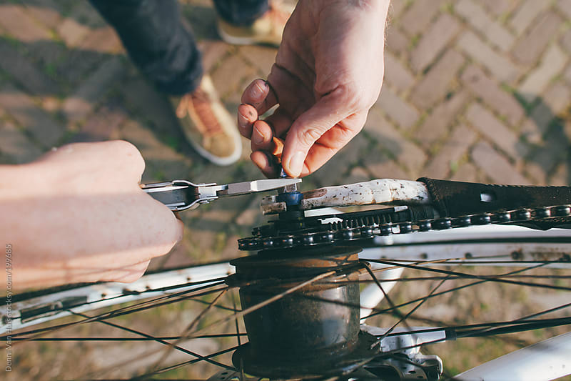 Fixing bicycle wheel with hands and tool by Denni Van Huis for Stocksy United