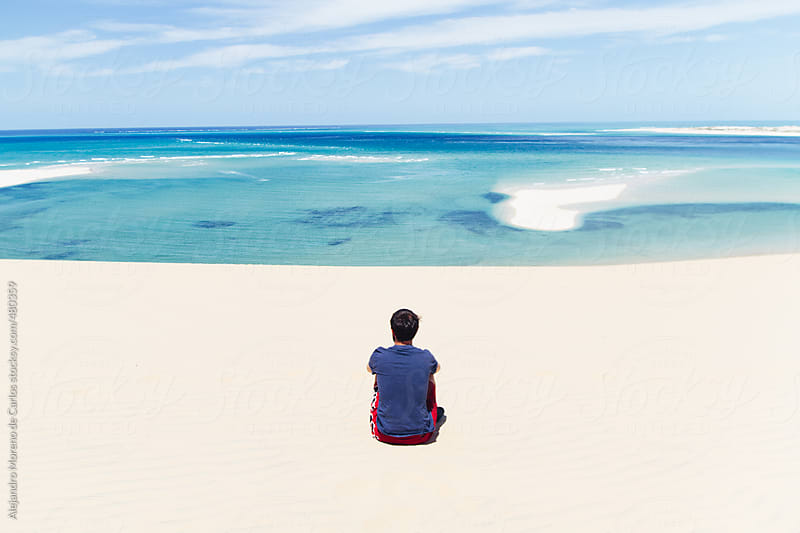 Young man sitting down on the sand looking at the ocean on an exotic tropical beach with turquoise water by Alejandro Moreno de Carlos for Stocksy United