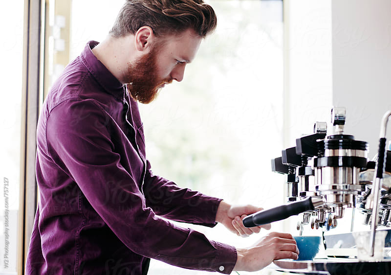 Young man making coffee in a cafe by W2 Photography for Stocksy United