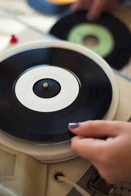Young woman placing vinyl on 60s record player by Pixel Stories for Stocksy United