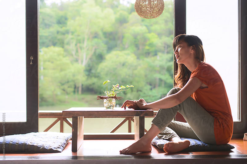 Young woman sits near window with green forest and lake by Lawren Lu for Stocksy United