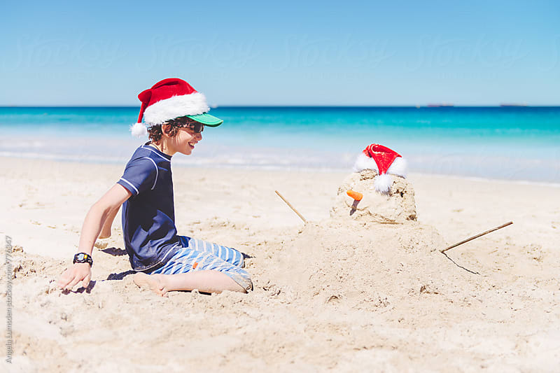 Boy smiling at a sand snowman at the beach at Christmas in Australia by Angela Lumsden for Stocksy United