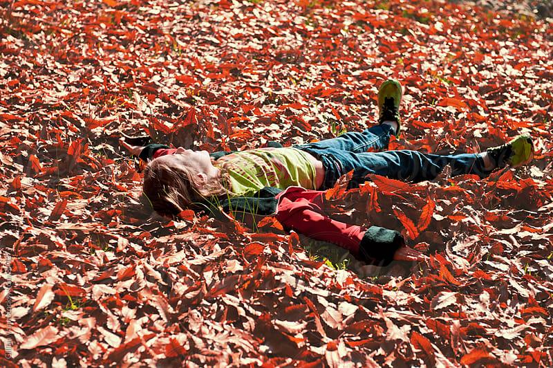 girl making a leaf angel by Gillian Vann for Stocksy United