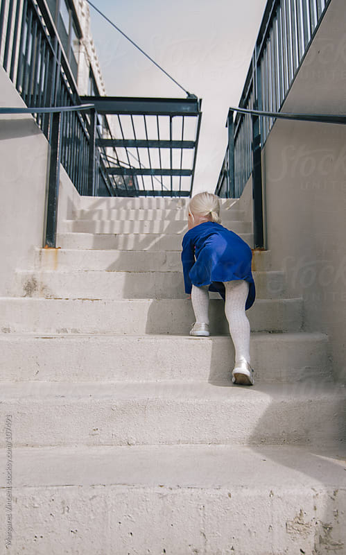 little girl climbs stairs by Margaret Vincent for Stocksy United