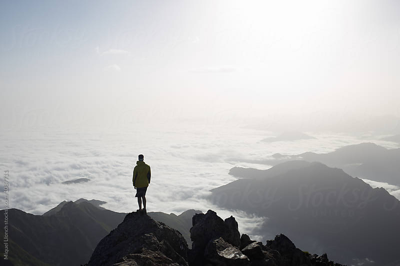 Silhouette of a young man at the top of the mountain with sea of clouds on the valley by Miquel Llonch for Stocksy United