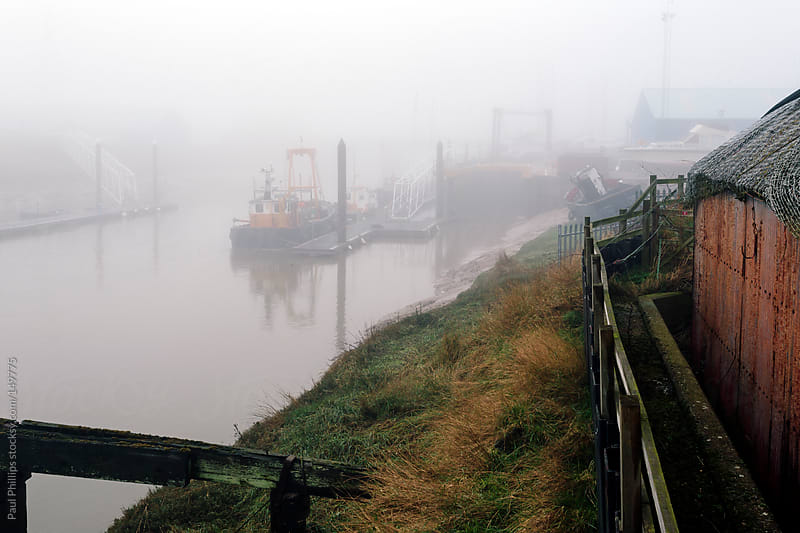Fog covering a docking area on a river  by Paul Phillips for Stocksy United