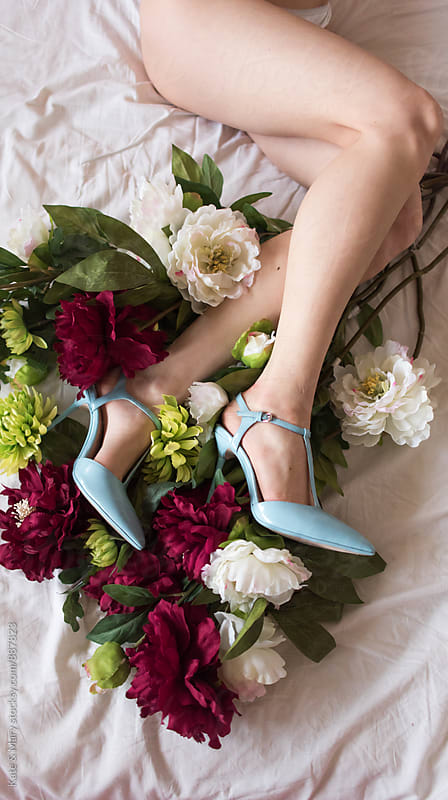 Close up of woman with blue shoes and flowers by Kate & Mary for Stocksy United
