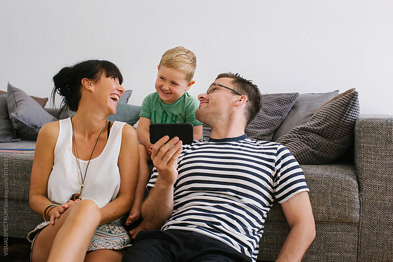 Family at Home - Young Parents With Small Boy Laughing Hard by Julien L. Balmer for Stocksy United