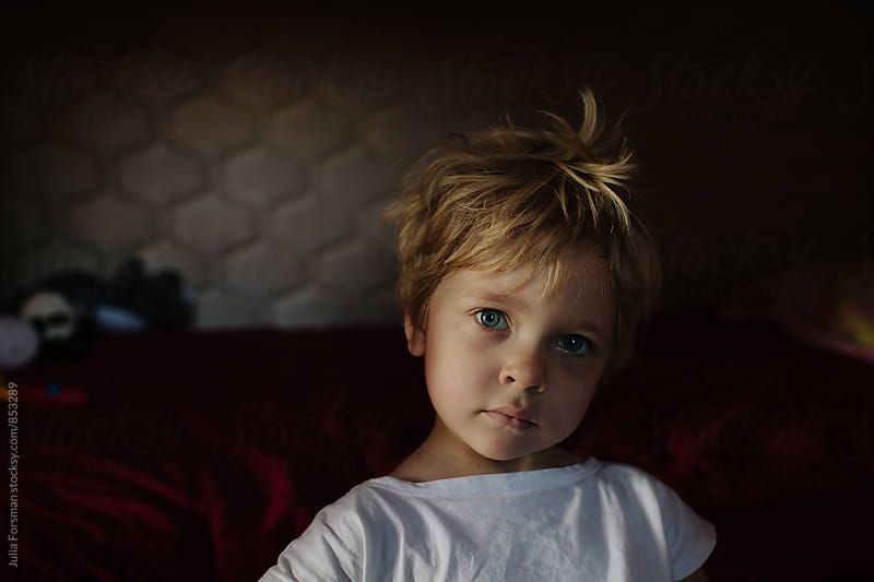 Little girl sitting beside her bed in early morning light. by Julia Forsman for Stocksy United
