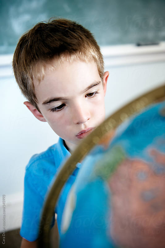 Child looks at a globe in a classroom by Cara Dolan for Stocksy United