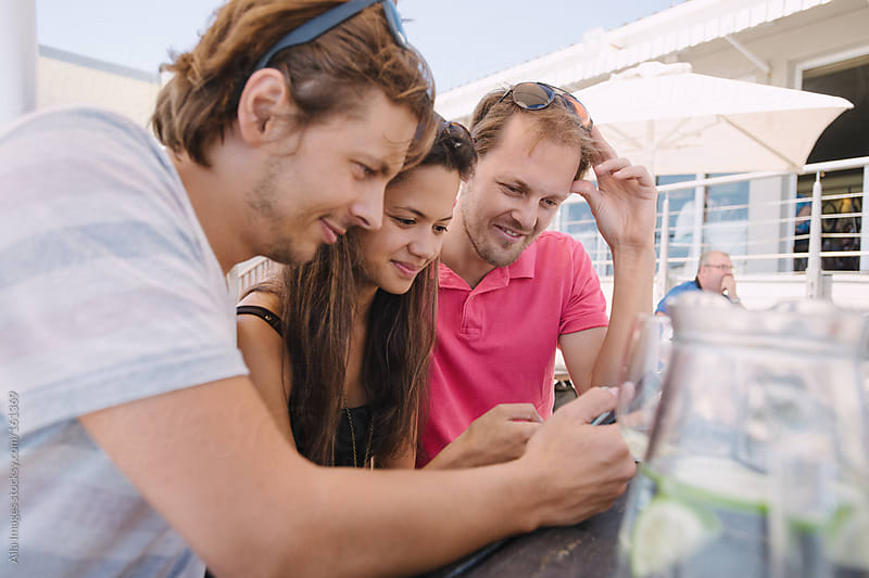 Three friends sharing on their mobile devices by Aila Images for Stocksy United