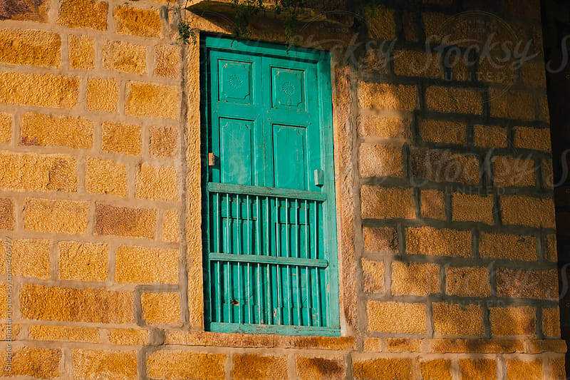 Closed green window on a yellow wall. by Shikhar Bhattarai for Stocksy United