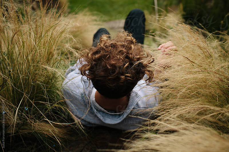 Male model sitting in long grass. by Julia Forsman for Stocksy United