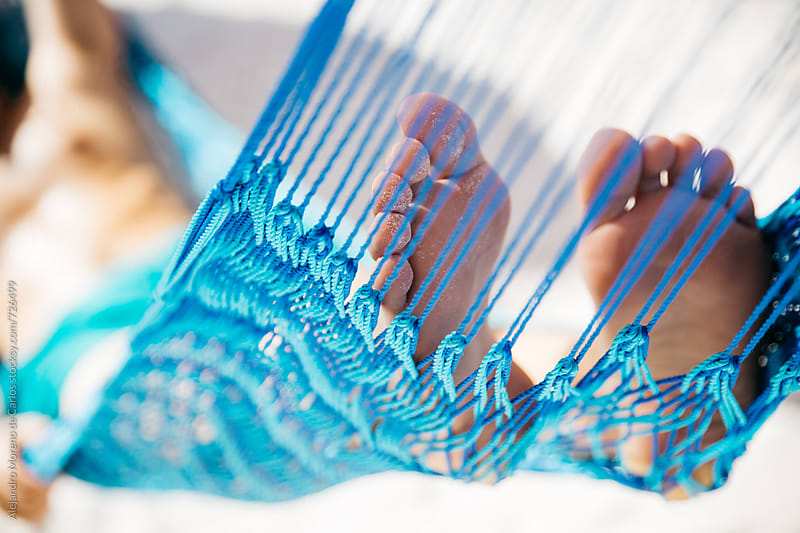 Closeup shot of feet on a blue hammock by Alejandro Moreno de Carlos for Stocksy United