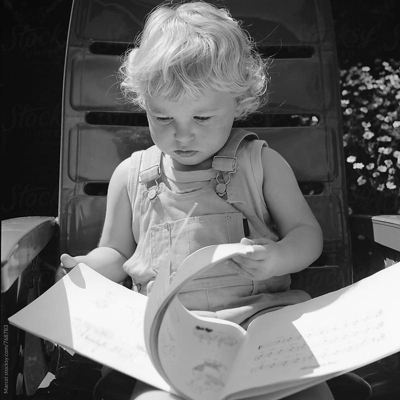 Blonde toddler girl looking in a book by Marcel for Stocksy United