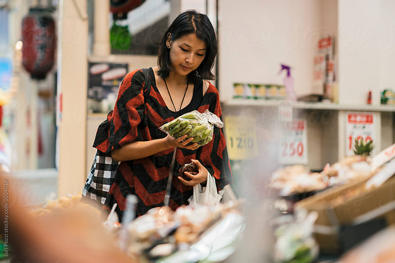 Young asian woman buying vegetables  by Juri Pozzi for Stocksy United