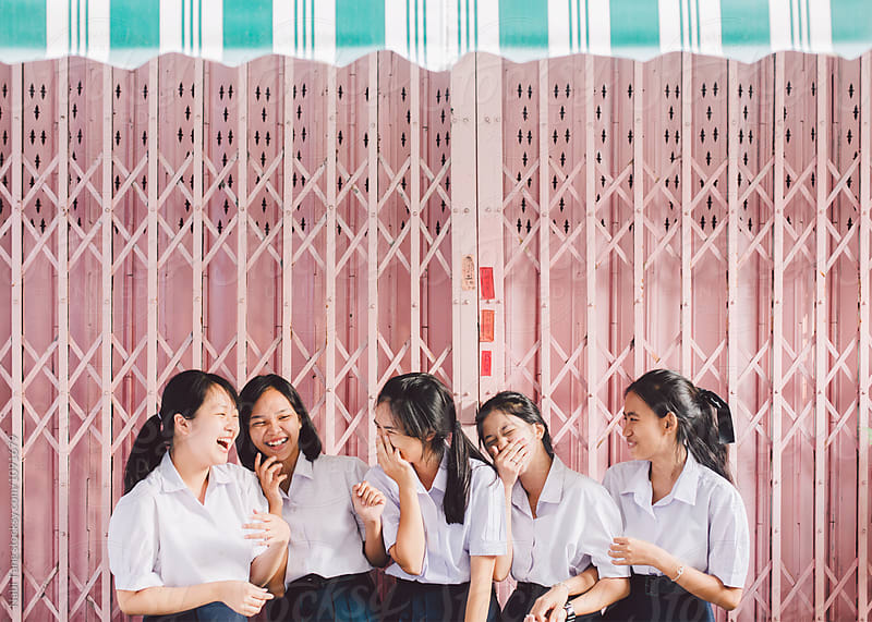 Asian high school girls standing in front of pastel pink garage door in Thailand by Nabi Tang for Stocksy United
