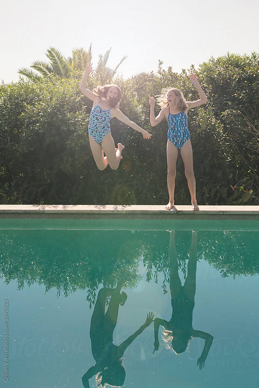 teenage girl jumping into a swimming pool, with her sister looking on laughing by Gillian Vann for Stocksy United