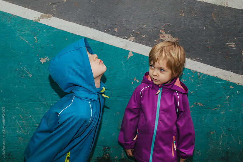 Bright, urban image of a little girl watching her big brother being silly. by Julia Forsman for Stocksy United