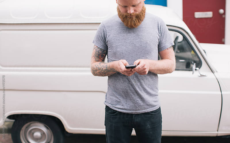 Bearded young man is texting on his cell phone with car on background by Melchior van Nigtevecht for Stocksy United
